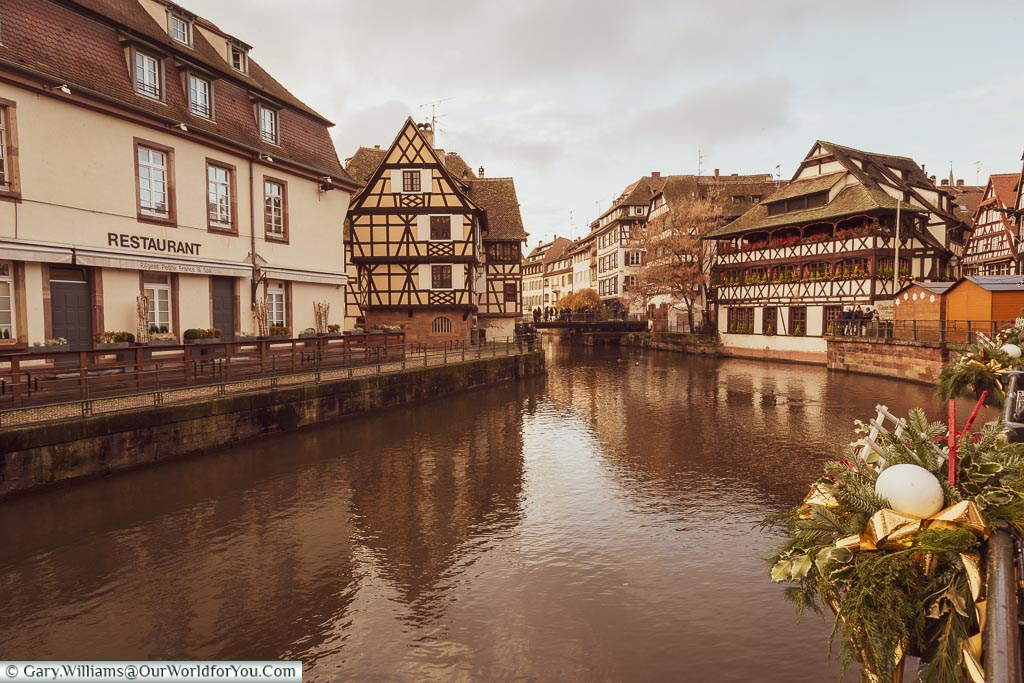 Overlooking the water in the Petite France region of Strasbourg with the waterside restaurant 'Maison des Tanners' with its decorated window boxes against the half-timbered building.  You can tell it's Christmas at the handrails are decorated with baubles and wreaths.