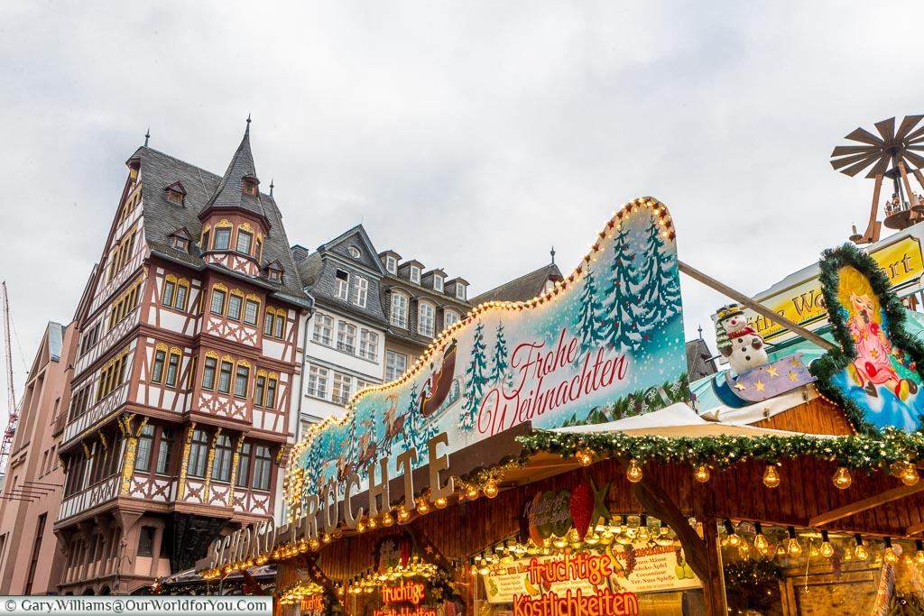 The ornate roof of a Christmas market stall in Römerberg in front of a half-timber building.