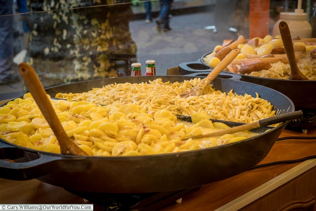 A large cast-iron open dish of Knepfle or Spaetzle, alongside another dish of Choucroute Garnie, on a Christmas market stall.