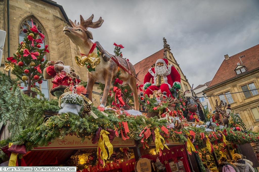 A stall decorated with red & gold ribbons and a single reindeer pulling Santa on his sleigh.