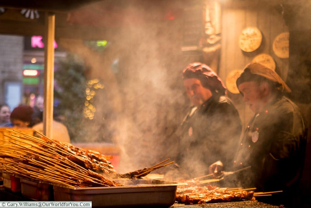 Metre long meat skewers being prepared on a smokey grill in Cologne, Germany