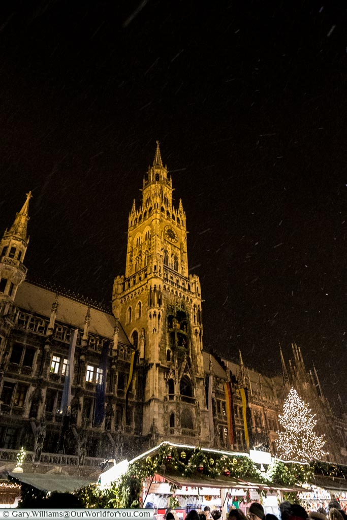 Looking up at the tower of Munich's Rathaus with markets stalls below as snow falls.