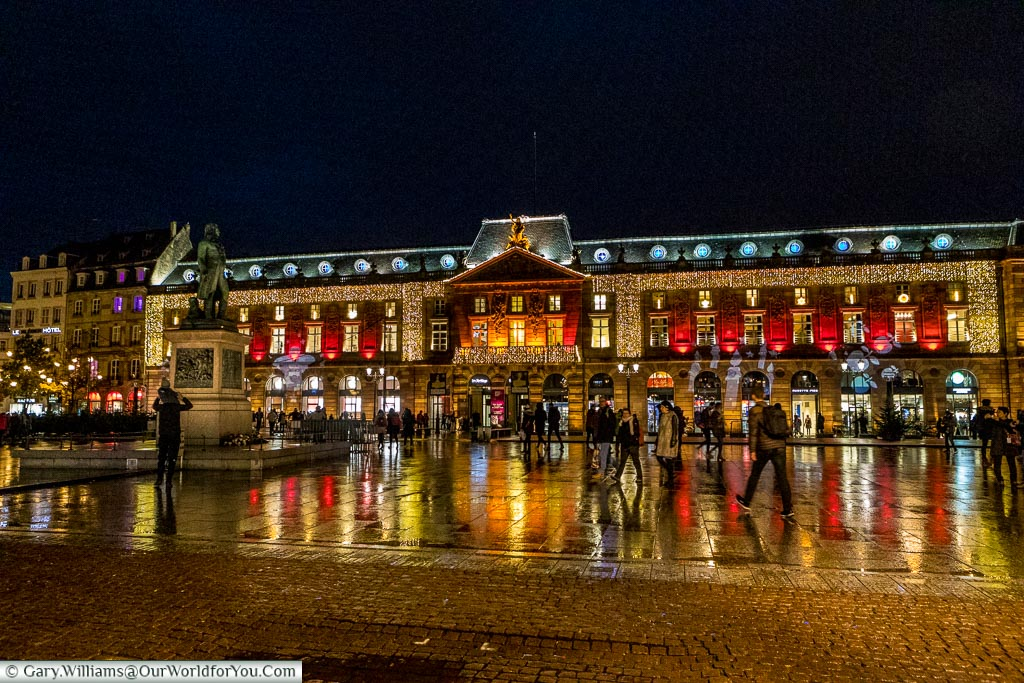 A scene across Place Kléber at night to the Aubette, a historic, mid-18th century, building brightly decorated in a mix of gold & red for Christmas.  The square in front of the building, damp from some earlier rain, reflects the lights of the building.