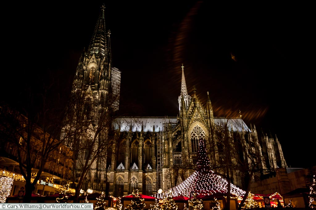 Looking up at the lit Dom Cathedral at night with the Christmas tree and its blanket of lights meeting the red-topped market huts.