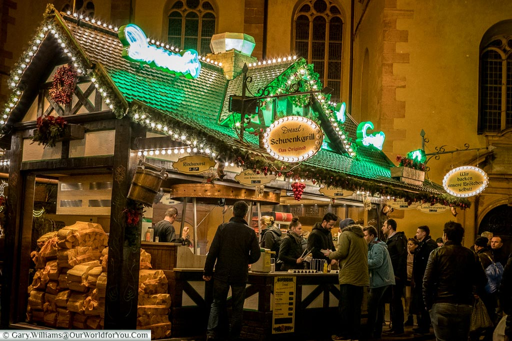 A food stall at night at the Christmas market in front of St. Catherine's Church.  The food is cooked over an open wood-fired grill and you can see the sacks of logs stacked at the end of the cabin.