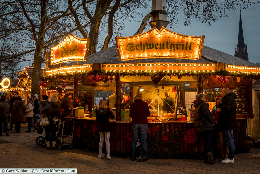 A grill stall on the quayside Christmas market at dusk, selling a variety of grilled sausages.
