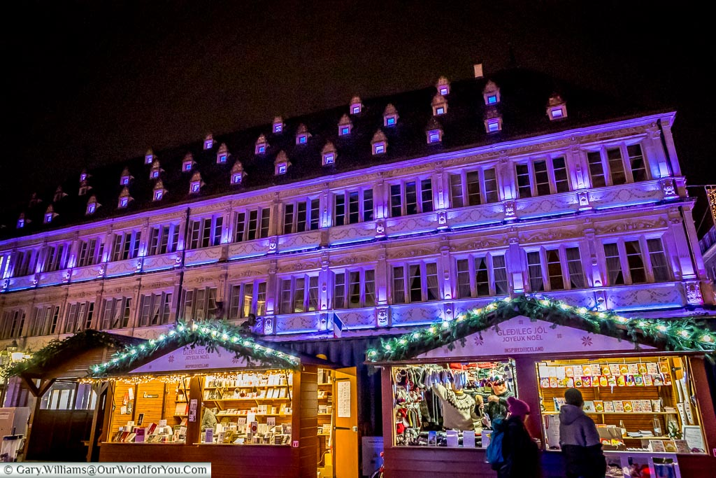 Christmas market stalls in the international market in Place Gutenberg in front of a historic building floodlit in a purple/lilac colour.