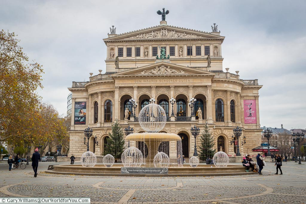 Frankfurt's old opera house from behind the Lucae-Brunnen fountain in Opernplatz.    The sandstone coloured neoclassical styled building was destroyed during the Second World War and completely rebuilt, reopening in 1981.
