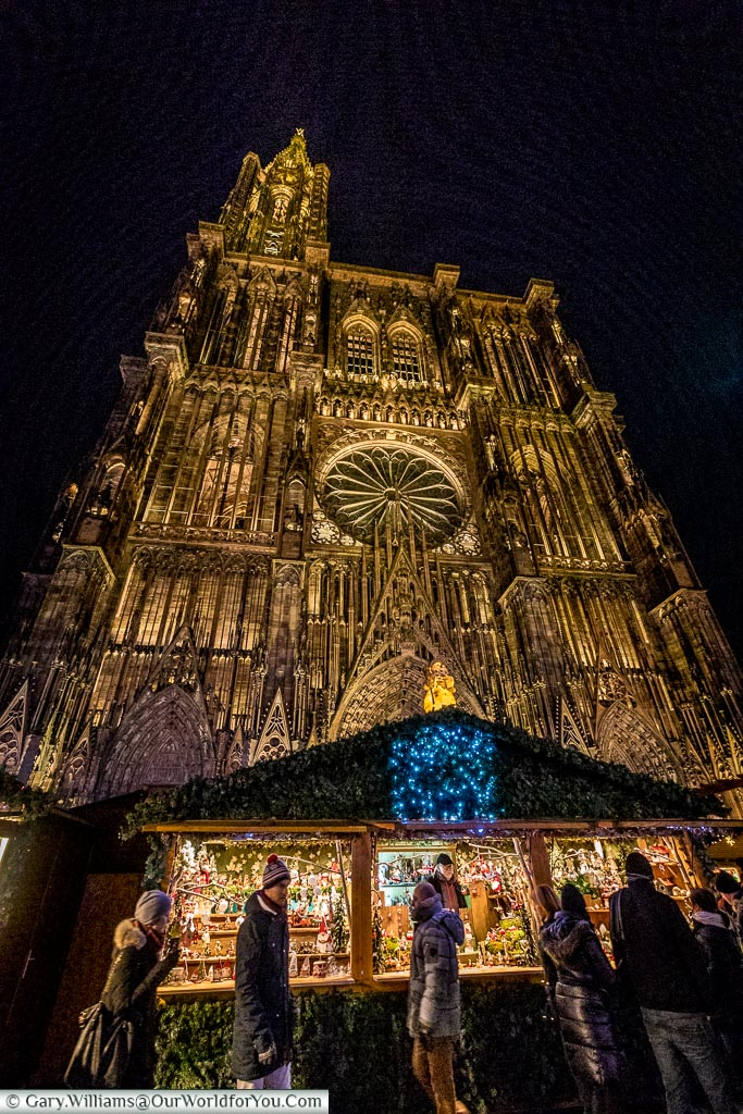 A low angle shot looking up at a Christmas market stall in front of the illuminated Cathedral of Strasbourg.