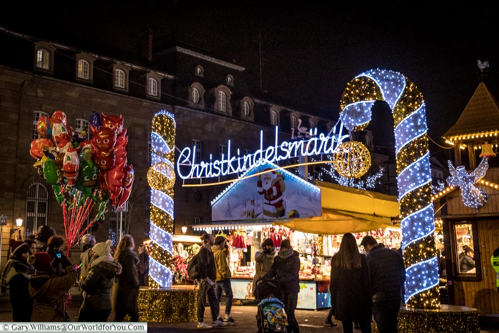 Folks mingling in front of the entrance to the Christkindelsmärik Christmas market, which is marked by a bright neon signed between two gold and silver striped candy canes created with fairy lights.