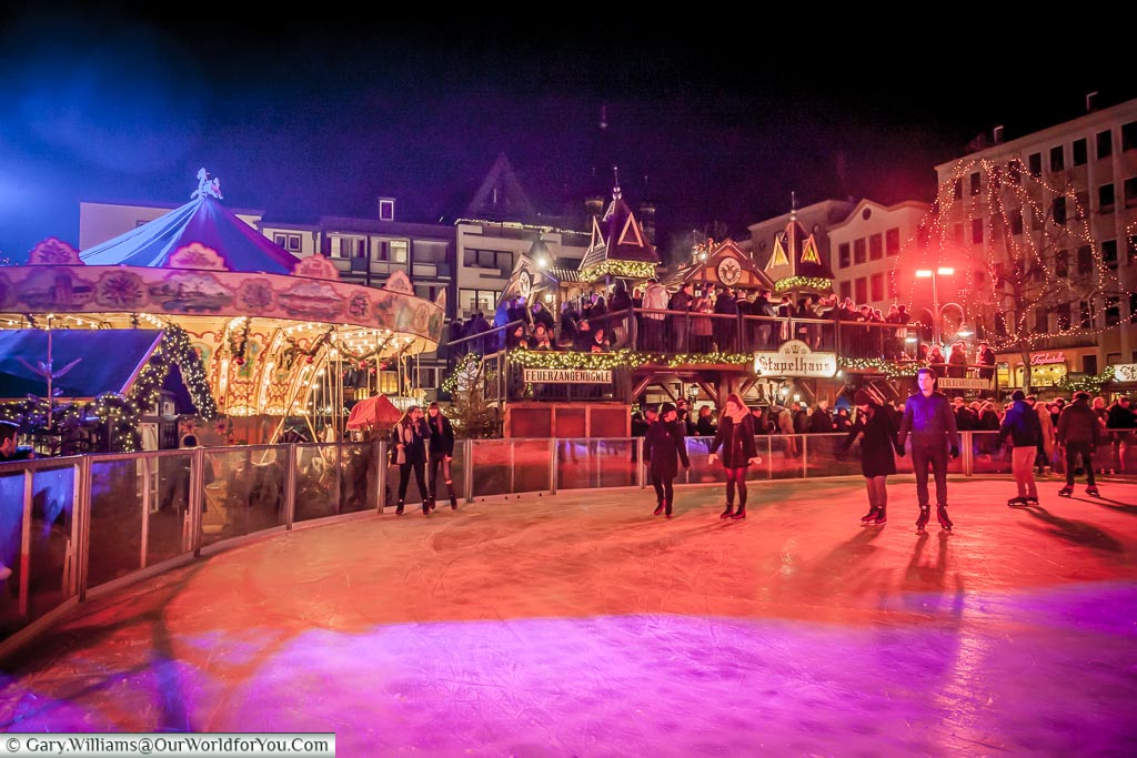 One of the circular ends to the ice rink in Cologne, lit at night,  overlooked by a carousel and the two-storey drinks cabin.