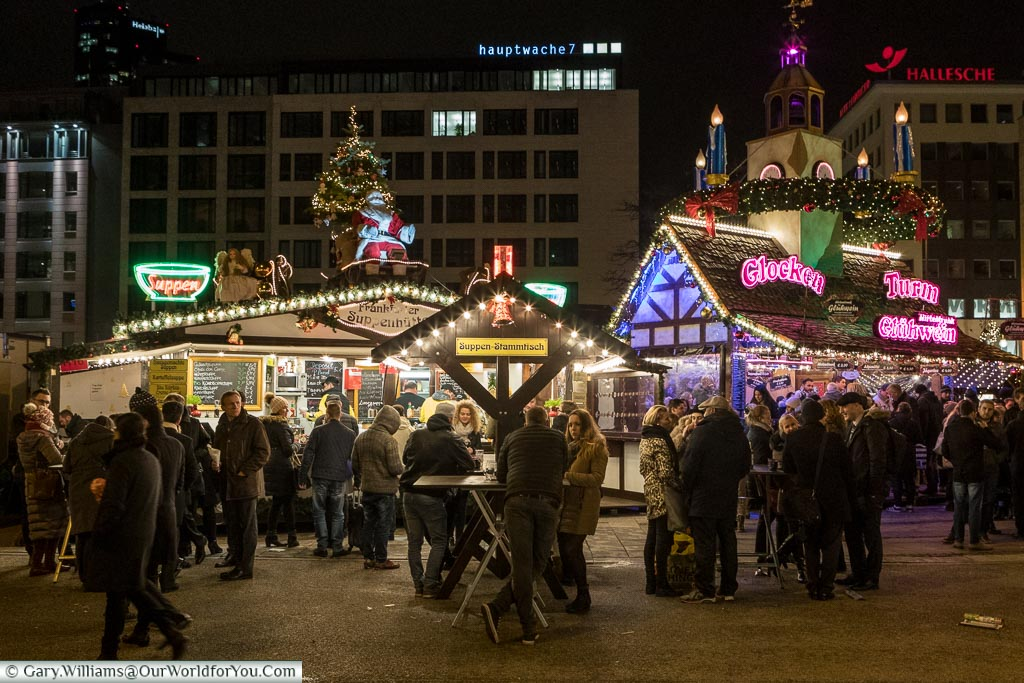 People milling about in front of a couple of the food & drink huts in the Christmas market in Plaza Hauptwache.  Bright neon lights decorate the ornate stalls.