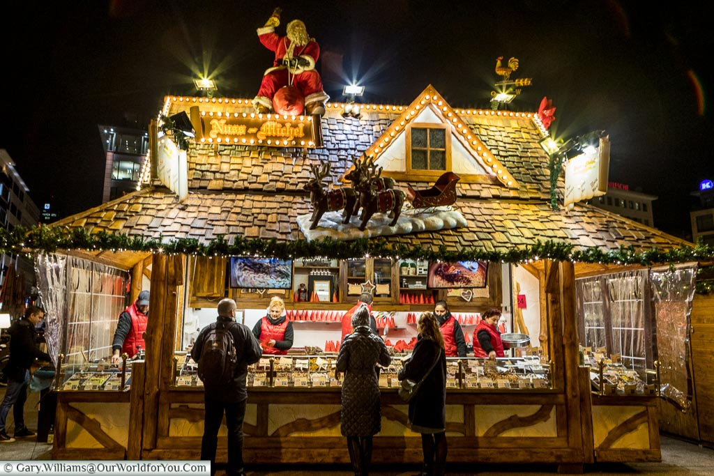 A stall on the Christmas markets selling roasted nuts that you literally can smell before you see.  The wooden hut has a jolly Santa and his reindeer perched on the tiled roof.