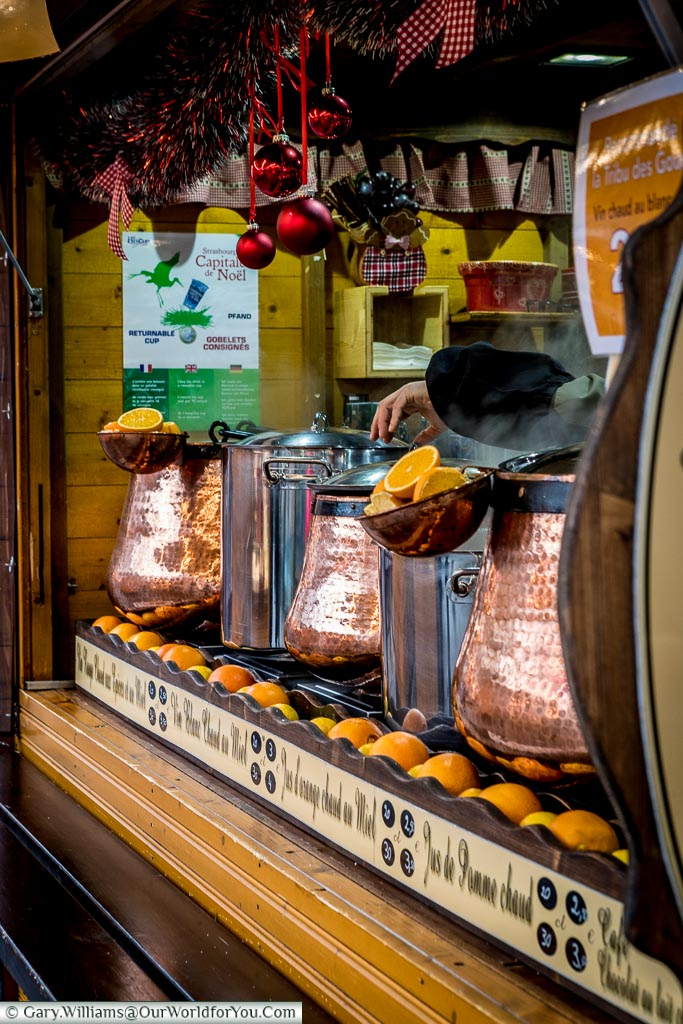 A view of a Christmas market stall with copper caldrons full of vin chaud.