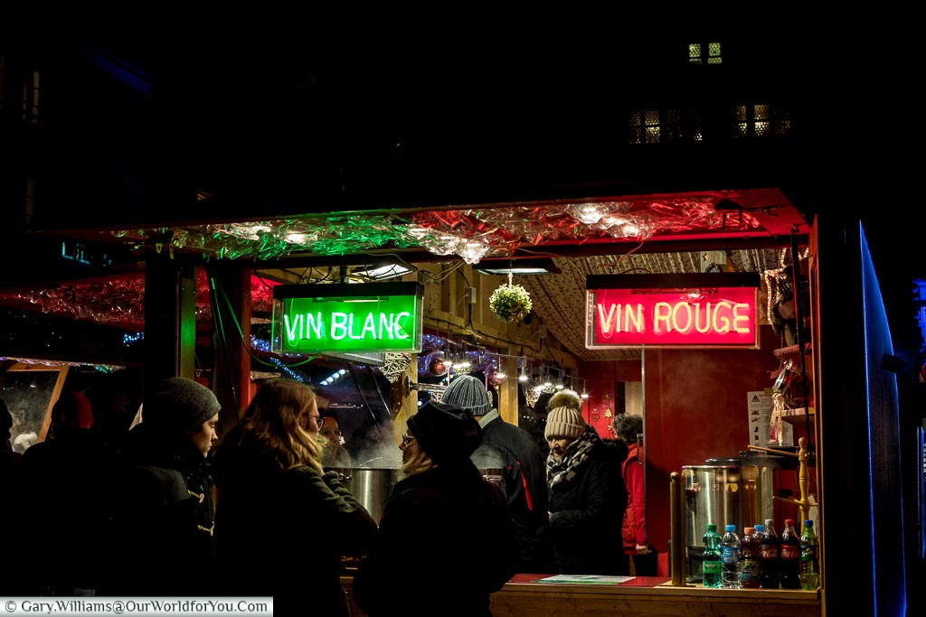 At the edge of a Christmas market drinks stall in the Place De La Cathédrale.  There are two neon signs, one offering vin blanc, the other vin rouge.