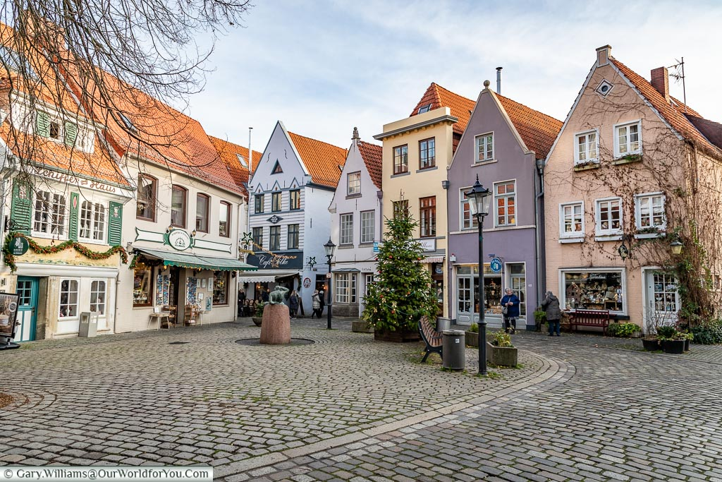 A Christmas tree in a quaint cobbled square, lined with tall thin pastel coloured historic buildings on two sides.