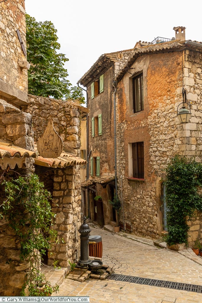 A narrow cobbled lane between rough stone provencal buildings in Tourrettes sur Loup