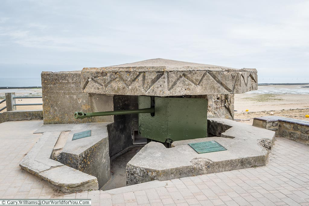 An artillery gun, mounted in a pillbox, at the edge of 'Juno' beach in Normandy.