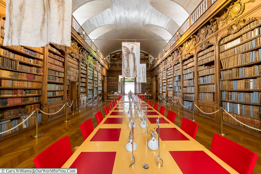 The reading room in Alençon public library. Ornately, Art Deco styled wooden bookcases line each side, with a more modern beach table with individual desk lights in the centre.  Stunning red chair and reading mat complete the view.