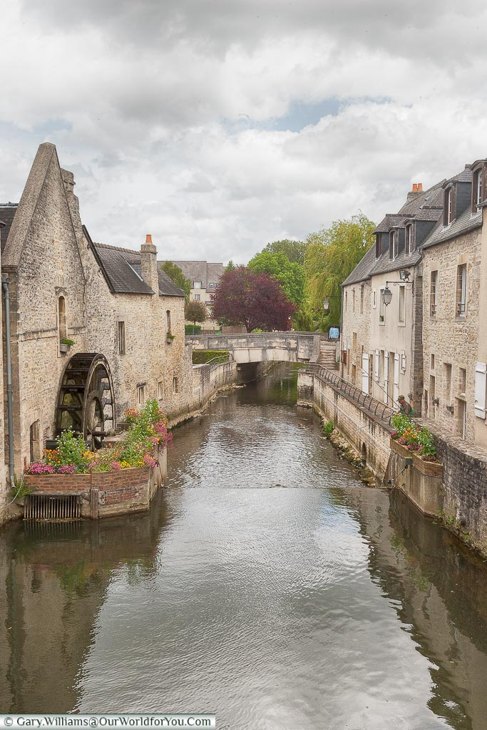 A view of a waterwheel, surrounded by flowers, in the River Aure in Bayeux.