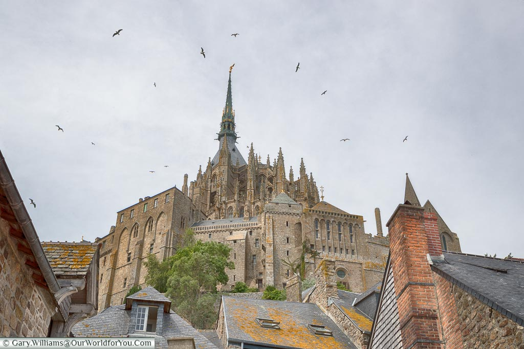 Birds circle the spire of the Mont-Saint-Michel Abbey, high on the hill, as the skies darken.