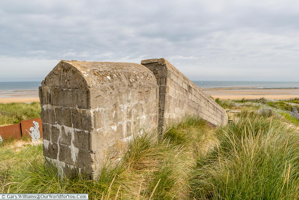 The edge of Cosy's Pillbox, on Juno Beach, Normandy with a view out to the sea on an overcast day.