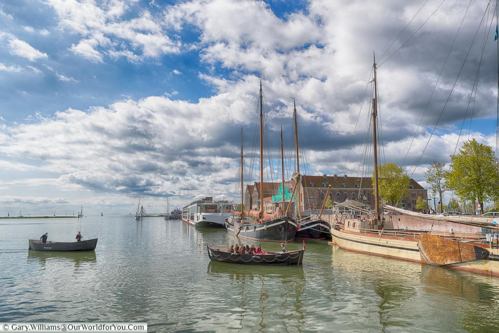 An idyllic scene of Hoorn harbour with sailing barges moored on the right and large rowing boats returning to dry land