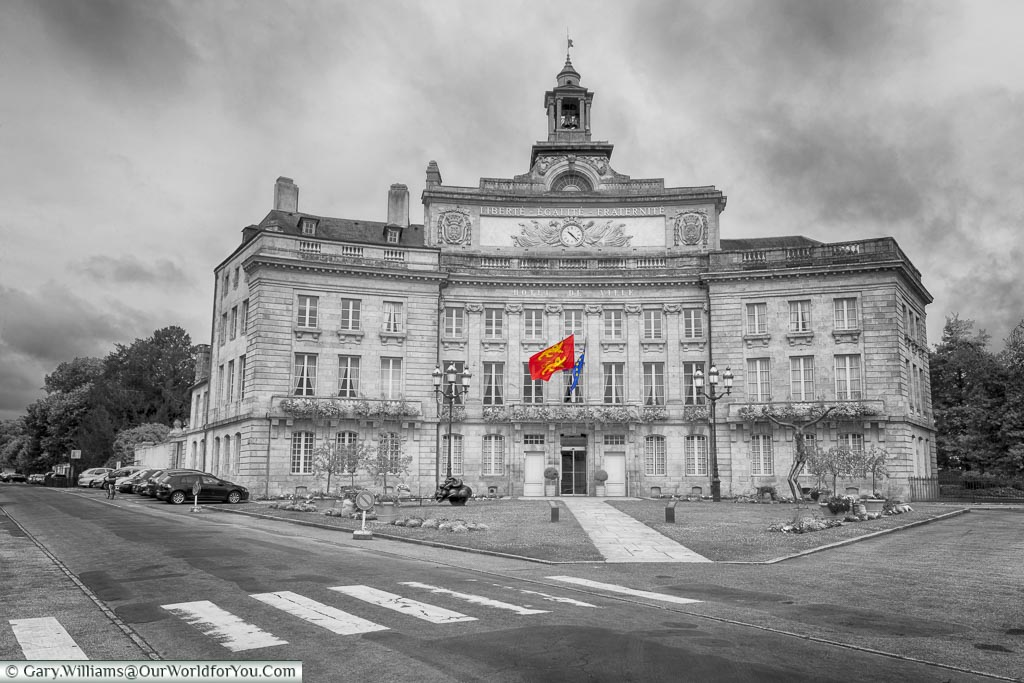 A partially desaturated image of the town hall, or L'Hôtel de Ville, of Alençon. The only colour in the shot is the red & yellow of the Normandy flag and the blue and yellow of the E.U. flag.