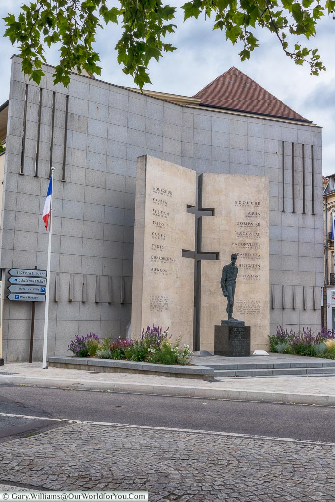 The memorial to General Leclerc in Alençon.  The brass statue of Leclerc stands in front of two large tables that list his campaigns, with a Cross of Lorraine extruded from join in them.