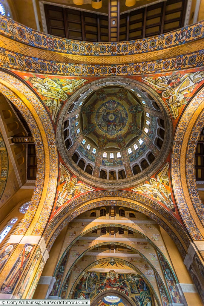 Inside the Basilica of St. Thérèse of Lisieux, looking up towards the ornately decorated dome.