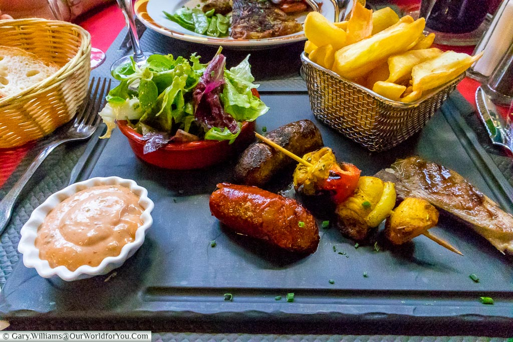 A meat feast served with a salad and chunky fries.
