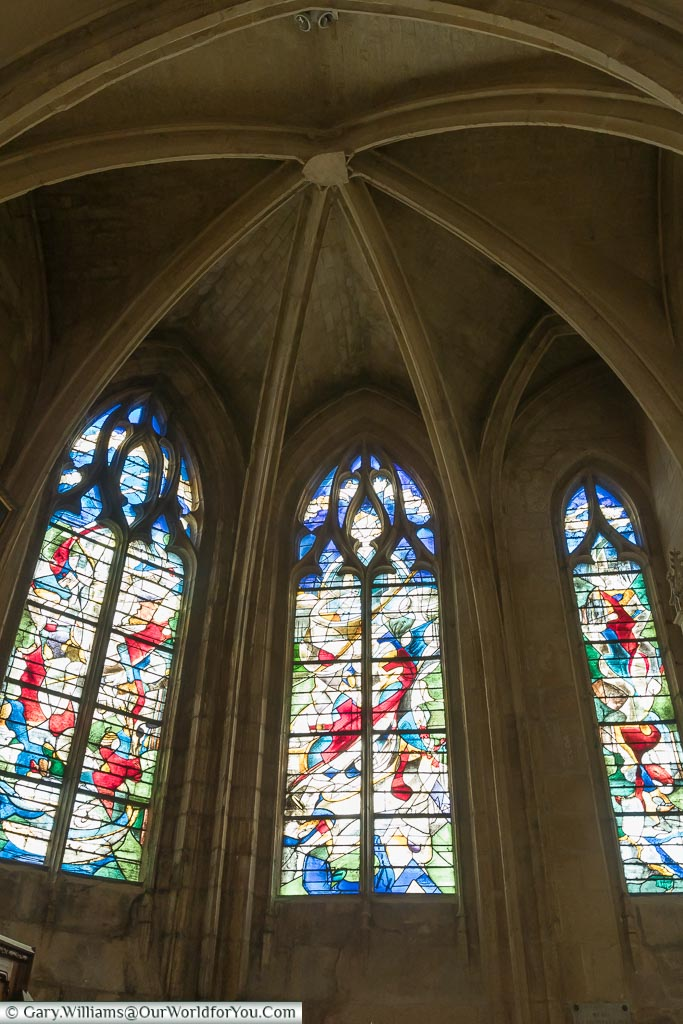 A modern art stained glass window under the vaulted ceiling of a chapel within the Basilica of Notre-Dame in Alençon, Normandy.