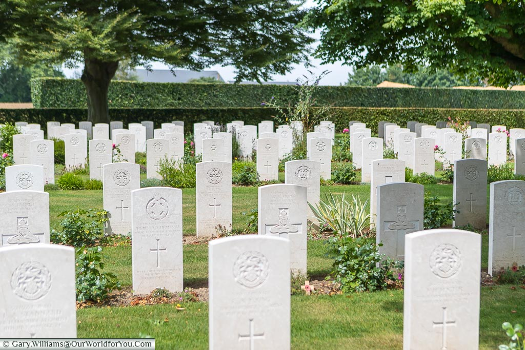 Row upon row of the white portland stone headstones of fallen Commonwealth Servicemen in the Bayeaux British military cemetery in Normandy.
