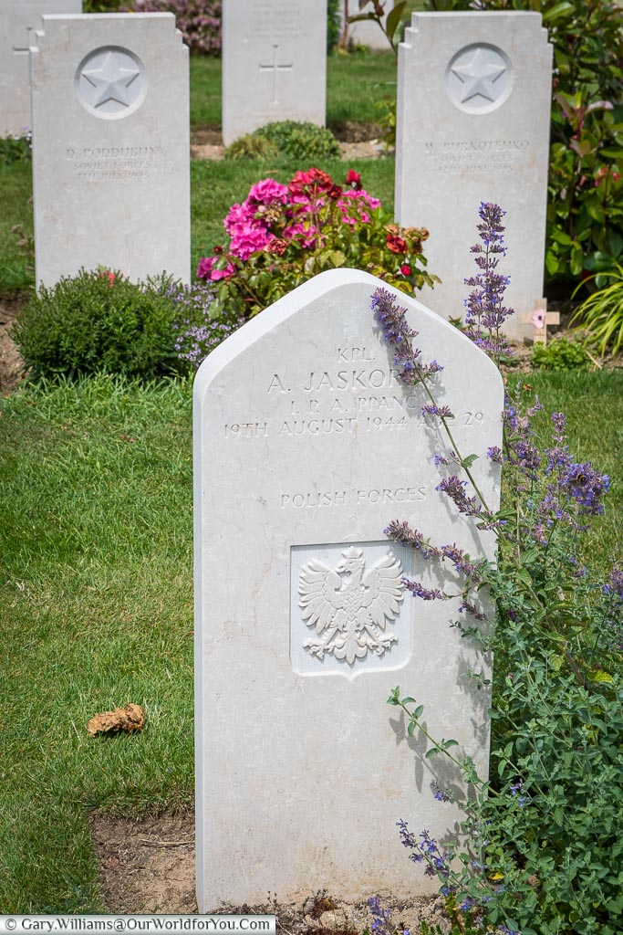 A headstone, in Bayeux Commonwealth Military Cemetery, to a Polish soldier, constructed of the same stone, but with a soft pointed top.