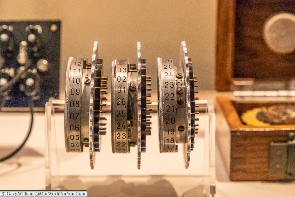 Three of the encryptions wheels, isolated from an Enigma machine, mounted on a perspex display stand in a display cabinet at Bletchley Park