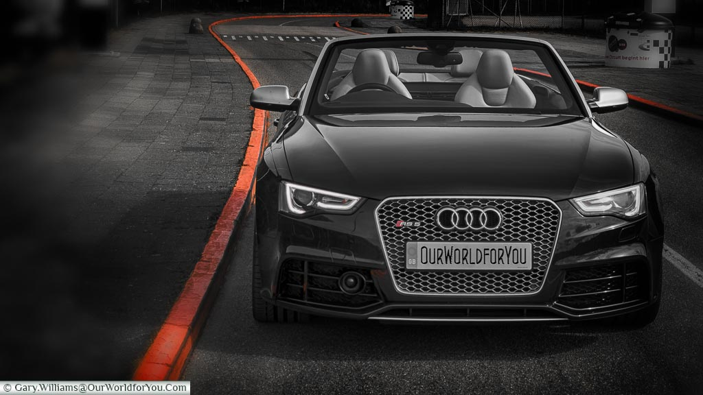 A stylised black, & white image of our Audi convertible parked at the edge of the road leading from the  Zandvoort Racing circuit, with the curbstones contrasted in Dutch Orange