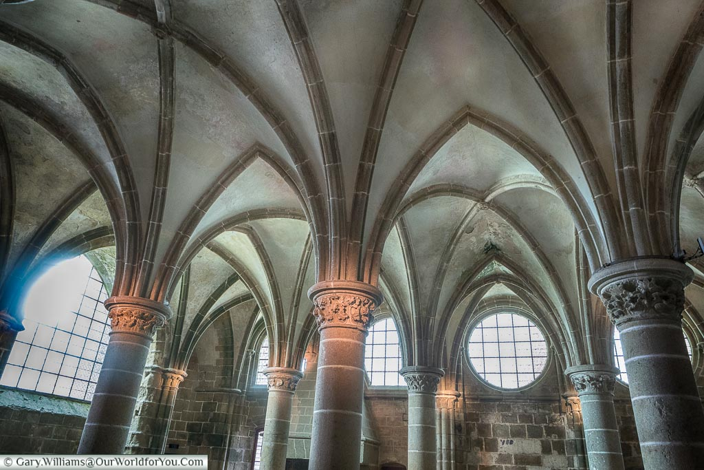 The Knights Hall of Mont-Saint-Michel Abbey, with its numerous columns supporting a vaulted ceiling.