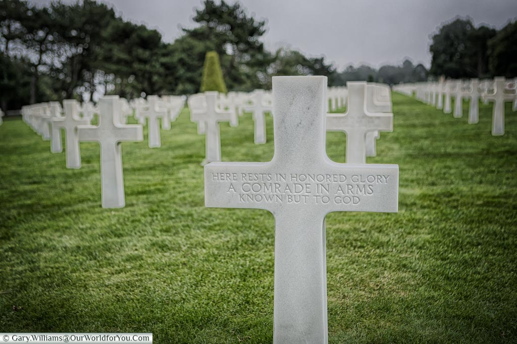 A marble cross in the Normandy American Cemetery to an unknown soldier with the inscription.  'Here rests in honored glory a comrade in arms know but to God'