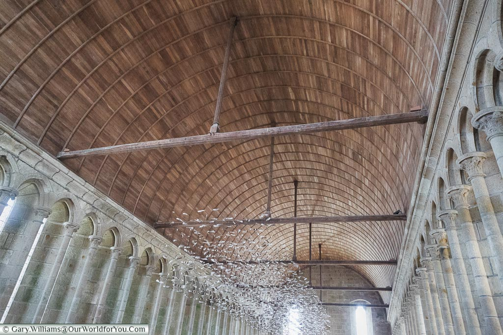 The roof of the refectory inside the Abbey of Mont-Saint-Michel.  The roof is lined with wood and is supported on either side by stone columns.