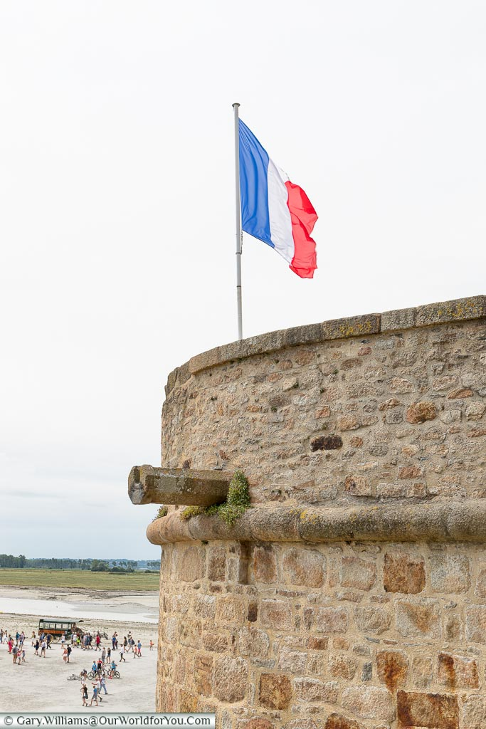 The French Tricolor flag flying high over the ramparts of Mont-Saint-Michel Abbey.