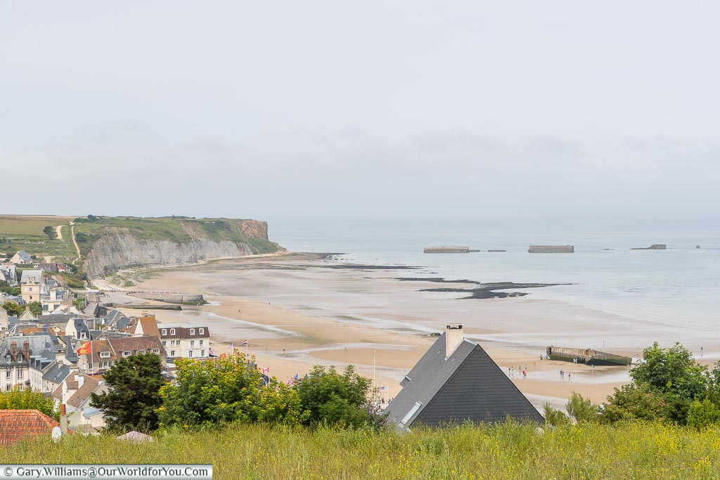The shoreline and bay of Arromanches from on high. You can view, both on the beach, and out to sea, the remains of the 'temporary' mulberry harbour constructed for the D-Day landings.