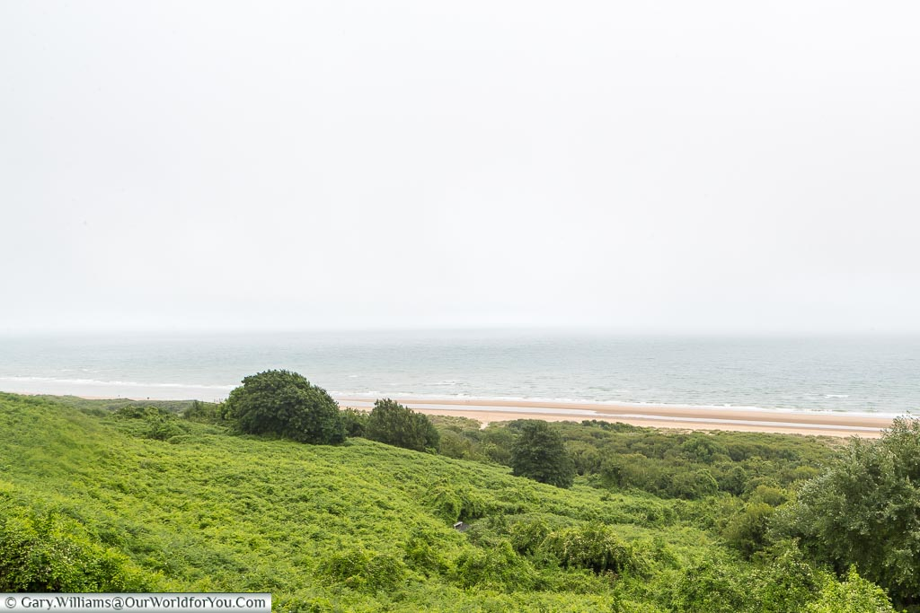 A view of the shoreline of 'Omaha' beach in Normandy, featuring a grassy mound, a thin strip of sand, and the ocean beyond.