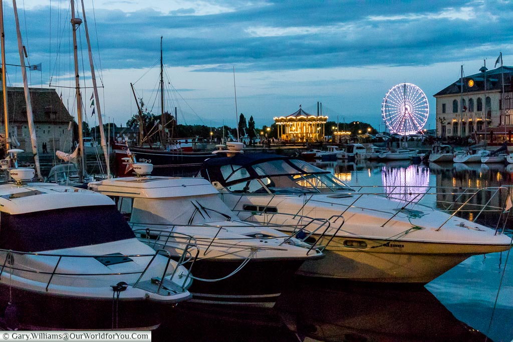 Boats in Honfleur's harbour at dusk with the illuminated carousel and Ferris wheel in the background.
