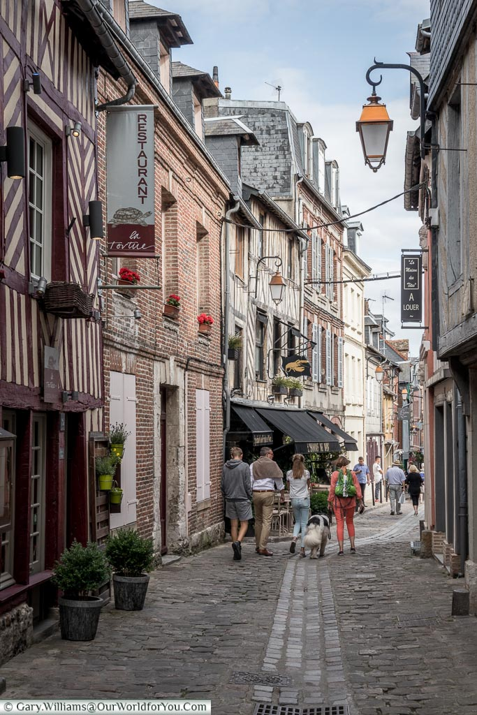 A winding, cobbled, lane running through the old town of Honfleur lined on either side by shops & cafes