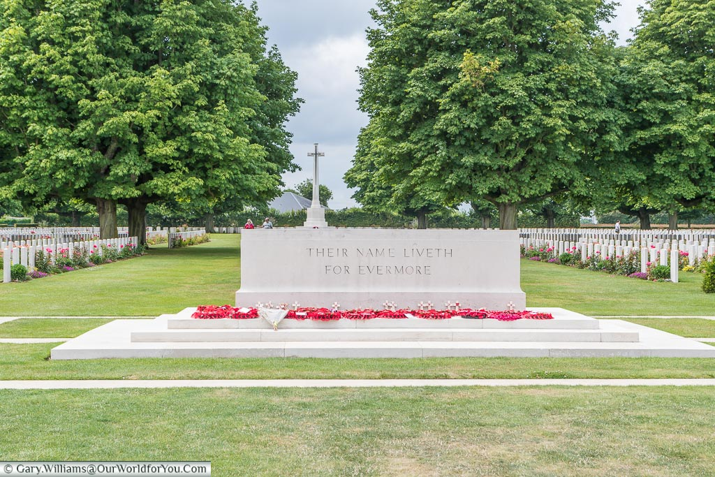 The 'Stone of Remembrance', with the 'Cross of Sacrifice' in the background, flanked on each side by headstones, at the Bayeux Commonwealth Military Cemetery in Normandy.