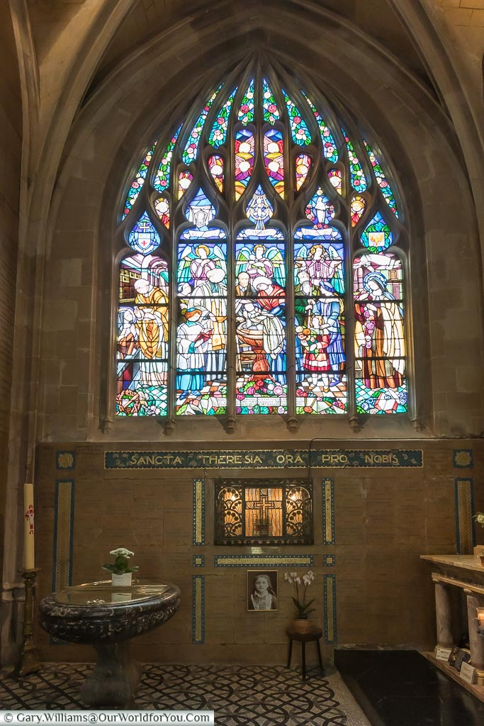 A stained glass window, next to the font, in the Basilica of Notre-Dame in Alençon, Normandy.