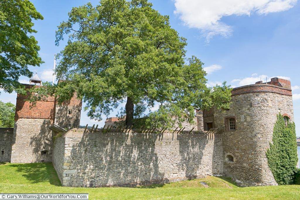 The stone wall that surrounds Upnor Castle from the land side, with the tower above the entrance, and another on the riverside edge.
