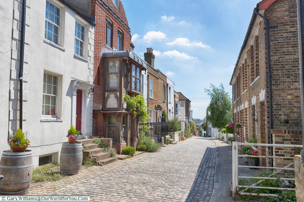 The cobbled high street, lined with historic brick-built houses, leading towards the River Medway on a sunny day.