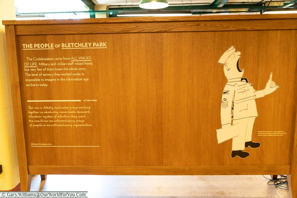A wooden information board explaining that Bletchley Park's people came from all walks of life, civilian and military, with a cartoon character, from the era, of a loud military figure.