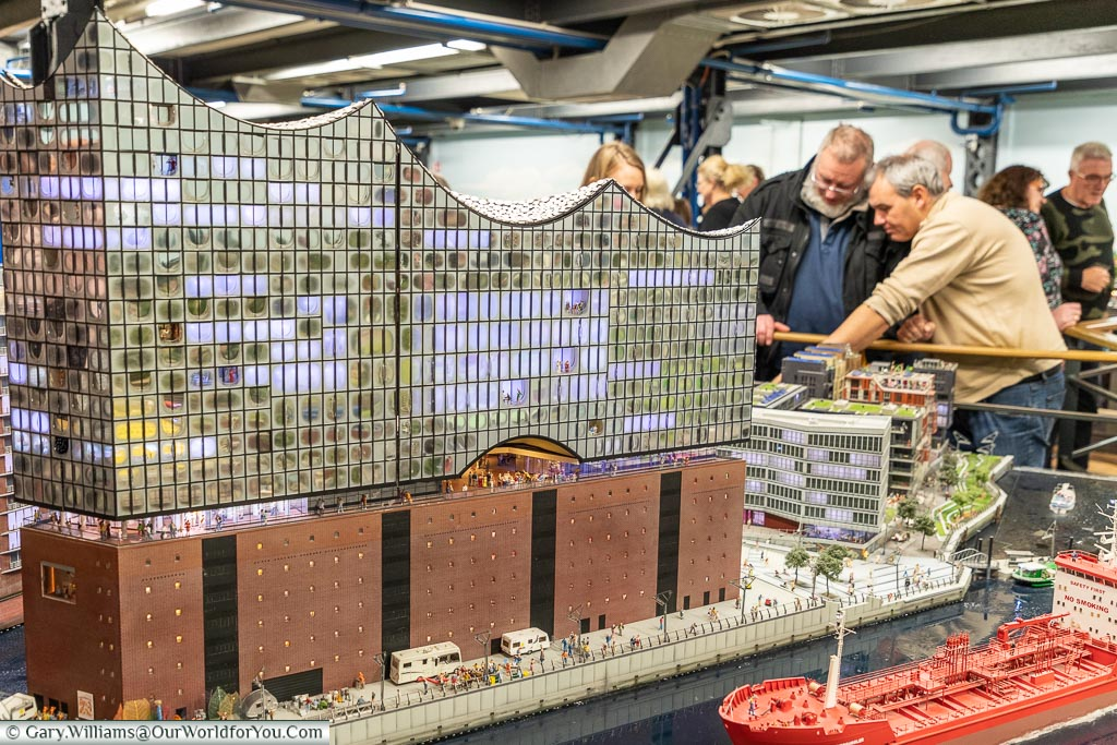 A scale model of the Elbphilharmonie at Miniatur Wunderland, with visitors inspecting the level of detail in the exhibit.